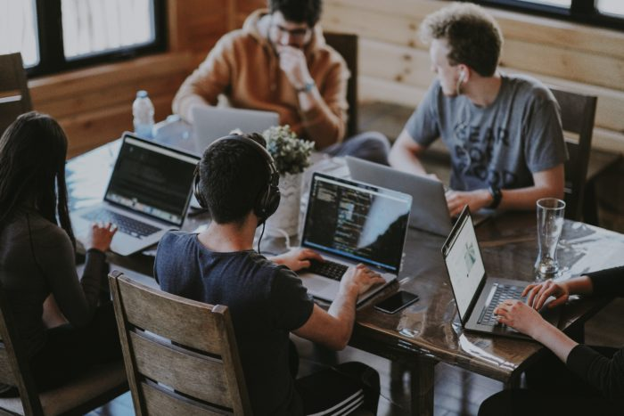 A photo of five developers sitting around a table, working.