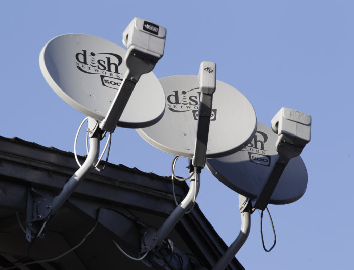 Photo of 3 TV satellite dishes on a rooftop.