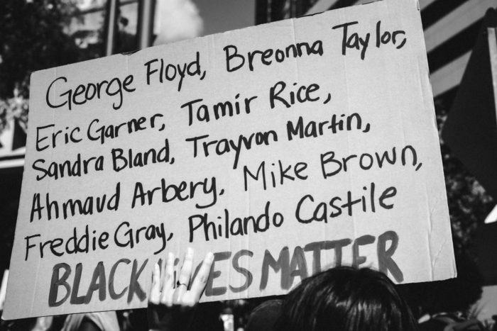 "A sign reads ""George Floyd, Breonna Taylor, Eric Garner, Tamir Rice, Sandra Bland, Trayvon Martin, Ahmaud Arbery, Mike Brown, Freddie Gray, Philando Castile BLACK LIVES MATTER."""